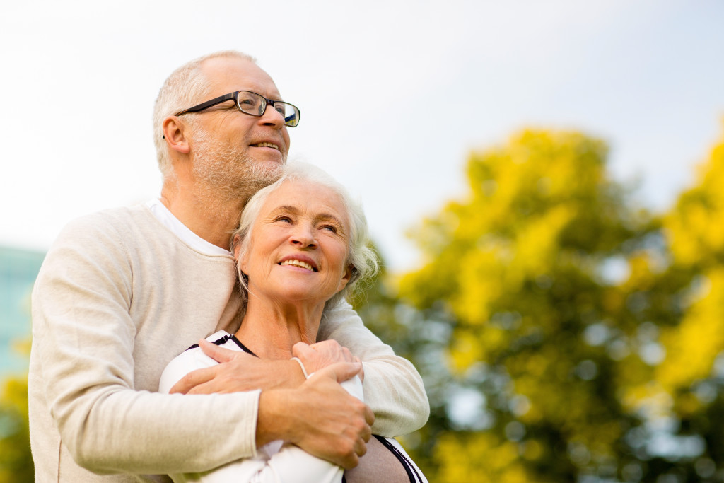 family, age, tourism, travel and people concept - senior couple hugging in park